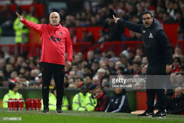 Mike Phelan, Assistant Manager of Manchester United and David Wagner, Manager of Huddersfield Town reacts during the Premier League match between...