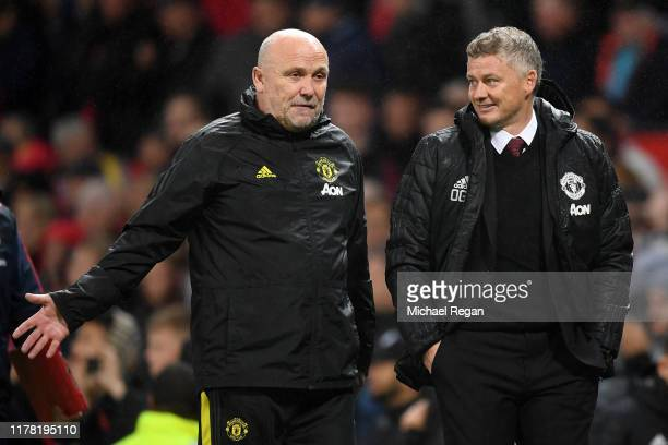 Mike Phelan, assistant manager speaks with Ole Gunnar Solskjaer, Manager of Manchester United as they walk off the pitch at half time during the...