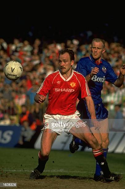 Mike Phelan of Manchester United intercepts the ball from Andy Ritchie of Oldham during the FA Cup Semi-Final at Villa Park in Birmingham, England....