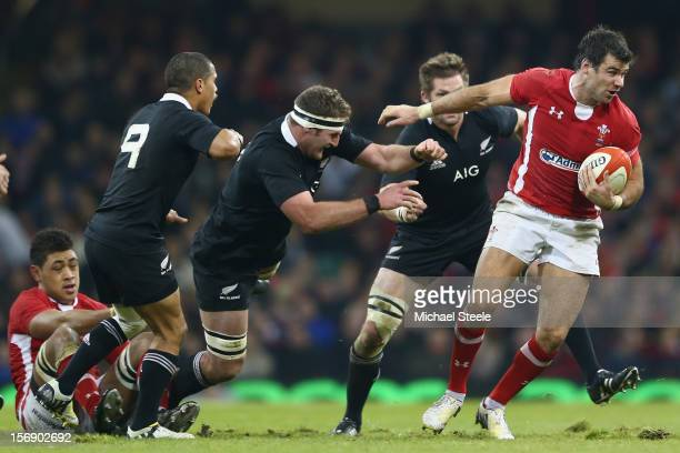 Mike Phillips of Wales pulls away from the challenge of Richie McCaw , Kieran Read and Aaron Smith of New Zealand during the International match...