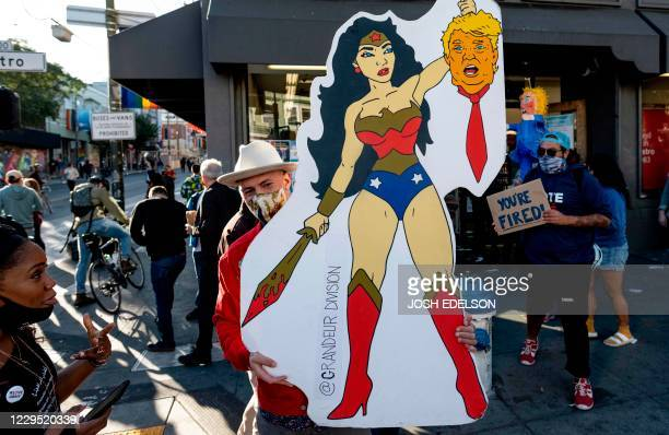 Mike Picot holds up an illustration of Wonder Woman holding the head of Donald Trump as people celebrate Joe Biden being elected President of the...