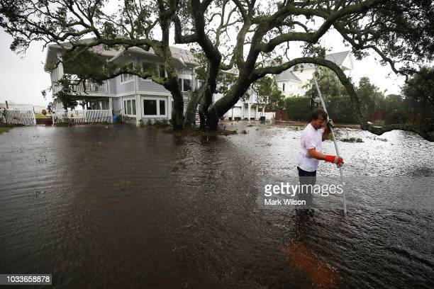 Mike Pollack searches for a drain in the yard of his flooded waterfront home a day after Hurricane Florence hit the area on September 15 2018 in...