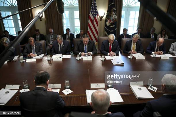 Mike Pompeo US secretary of state center left reads a prayer next to US President Donald Trump during a meeting in the Cabinet Room of the White...
