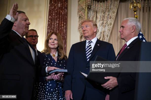 Mike Pompeo US secretary of state left is sworn in by US Vice President Mike Pence right with US President Donald Trump center Susan Pompeo third...