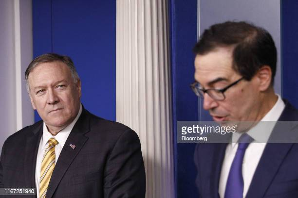 Mike Pompeo US secretary of state left listens as Steven Mnuchin US Treasury secretary speaks during a White House press briefing in Washington DC US...