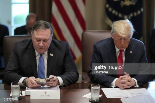 Mike Pompeo US secretary of state left reads a prayer next to US President Donald Trump during a meeting in the Cabinet Room of the White House in...