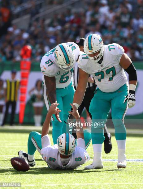 Mike Pouncey and Jesse Davis help Jay Cutler of the Miami Dolphins to his feet against the New York Jets during the second half of an NFL game at...