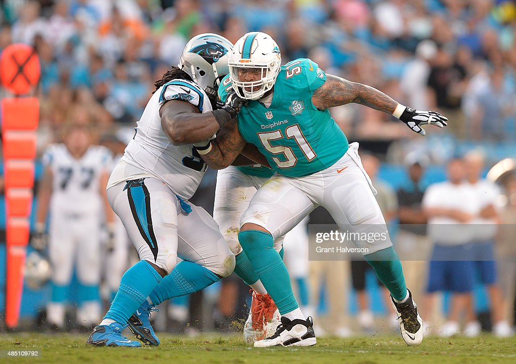 Mike Pouncey #51 of the Miami Dolphins blocks against the Carolina Panthers during their preseason NFL game at Bank of America Stadium on August 22, 2015 in Charlotte, North Carolina.