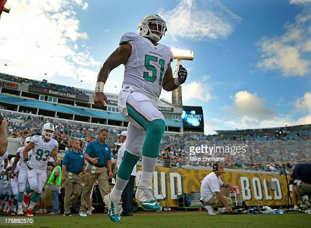Mike Pouncey of the Miami Dolphins leads the team onto the field during a preseason game against the Jacksonville Jaguars at EverBank Field on August...