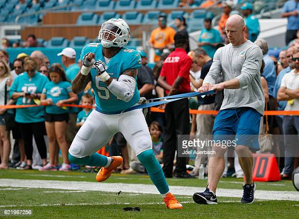 Mike Pouncey of the Miami Dolphins warms up prior to the game against the New York Jets on November 6 2016 at Hard Rock Stadium in Miami Gardens...