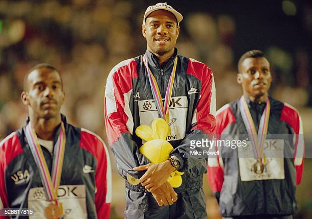 Mike Powell of the United State celebrates on the podium with silver medallist Carl Lewis and bronze medallist Larry Myricks after making his world...