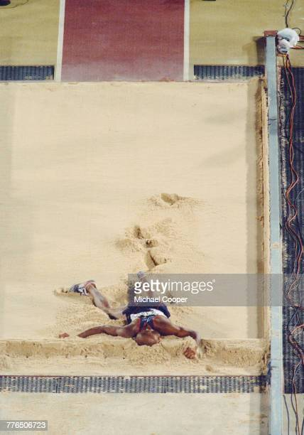 Mike Powell of the United States writhes in agony in the sand pit after injuring himself in the Men's Long Jump event on 29 July 1996 during the XXVI...
