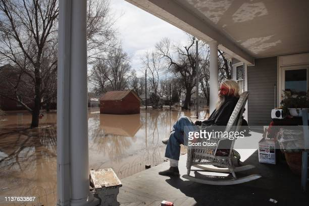 Mike Rasnic sits on the front porch of his home which is surrounded by floodwater on March 22 2019 in Craig Missouri Midwest states are battling some...