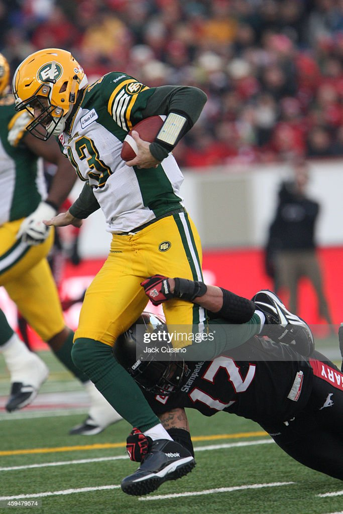 Mike Reilly #13 of the Edmonton Eskimos is tackled by Juwan Simpson #12 of the Calgary Stampeders during the divisional finals at McMahon Stadium on November 23, 2014 in Calgary, Alberta, Canada.