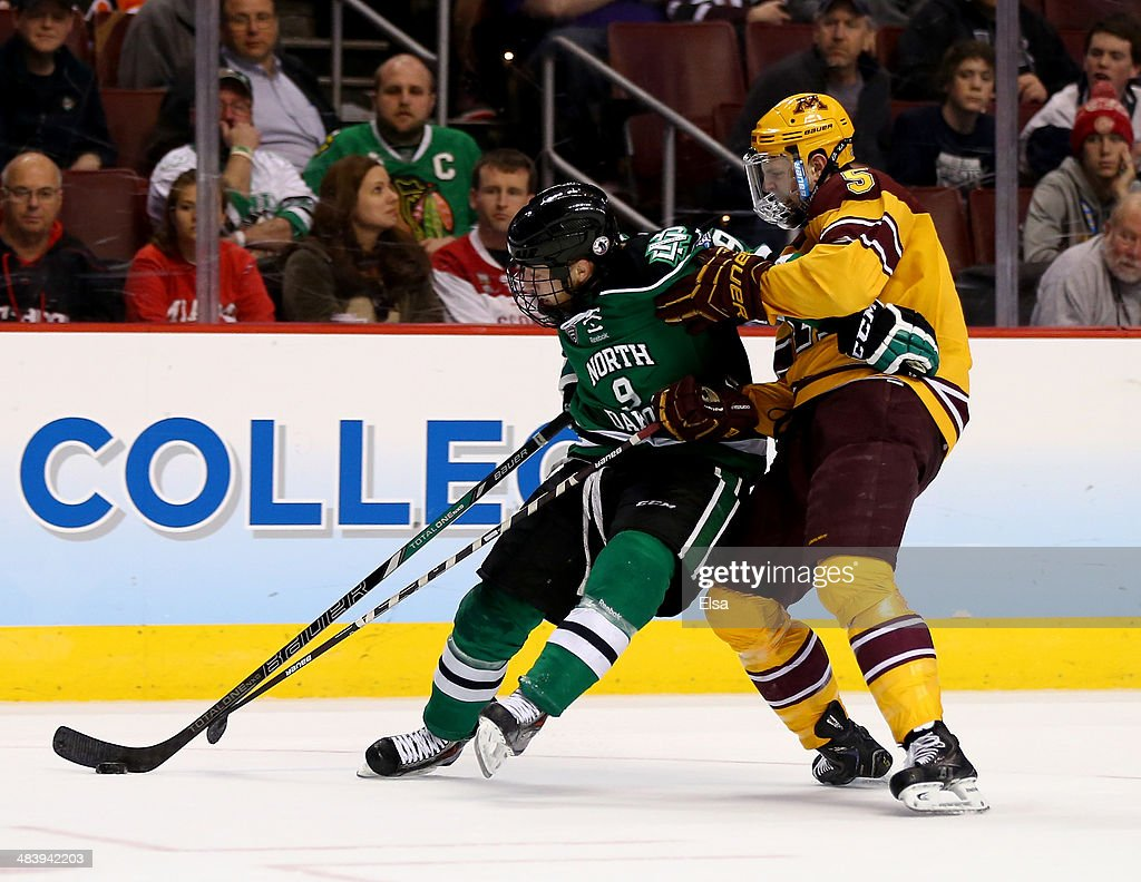Mike Reilly #5 of the Minnesota Golden Gophers is called for a holding penalty as Drake Caggiula #9 of the North Dakota Fighting Sioux tries to keep the puck in the final minutes of the game during the 2014 NCAA Division I Men's Hockey Championship Semifinal at Wells Fargo Center on April 10, 2014 in Philadelphia, Pennsylvania.The Gophers defeated the Fighting Sioux 2-1.