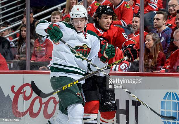 Mike Reilly of the Minnesota Wild and Andrew Shaw of the Chicago Blackhawks get physical by the boards in the first period of the NHL game at the...