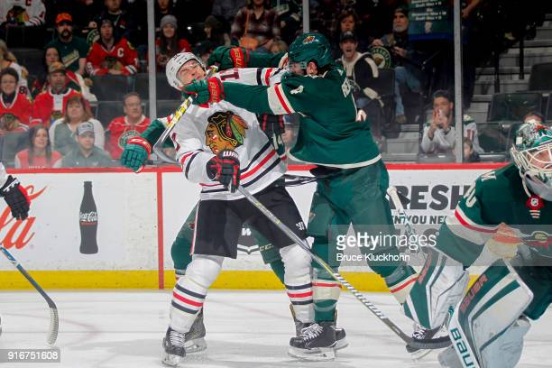 Mike Reilly of the Minnesota Wild cross checks Lance Bouma of the Chicago Blackhawks during the game at the Xcel Energy Center on February 10 2018 in...
