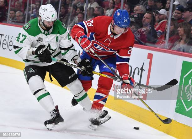 Mike Reilly of the Montreal Canadiens tries to keep the puck from Alexander Radulov of the Dallas Stars in the NHL game at the Bell Centre on March...