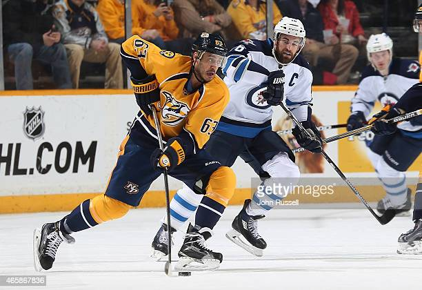 Mike Ribeiro of the Nashville Predators skates against Andrew Ladd of the Winnipeg Jets during an NHL game at Bridgestone Arena on March 7 2015 in...
