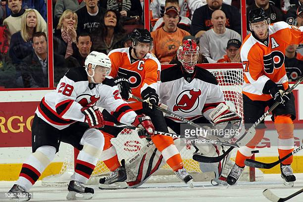Mike Richards and Jeff Carter of the Philadelphia Flyers attempt to deflect a shot past Anton Volchenkov and goaltender Johan Hedberg of the New...
