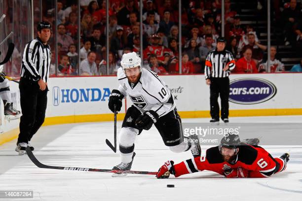 Mike Richards of the Los Angeles Kings goes for a loose puck as Andy Greene of the New Jersey Devils hits the ice during Game Five of the 2012 NHL...