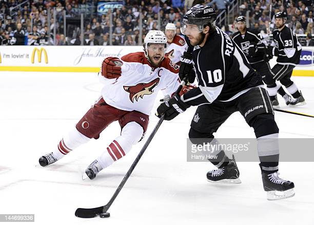 Mike Richards of the Los Angeles Kings moves the puck as Shane Doan of the Phoenix Coyotes rushes after him in the first period in Game Three of the...