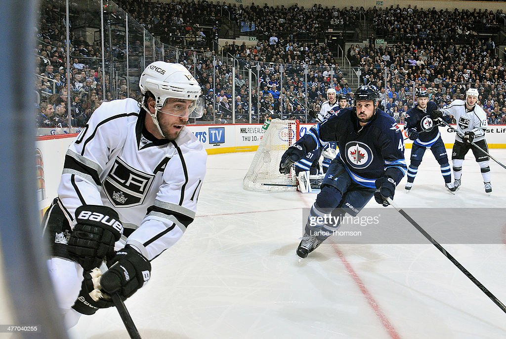 Mike Richards #10 of the Los Angeles Kings plays the puck along the boards as Zach Bogosian #44 of the Winnipeg Jets defends during third period action at the MTS Centre on March 6, 2014 in Winnipeg, Manitoba, Canada.