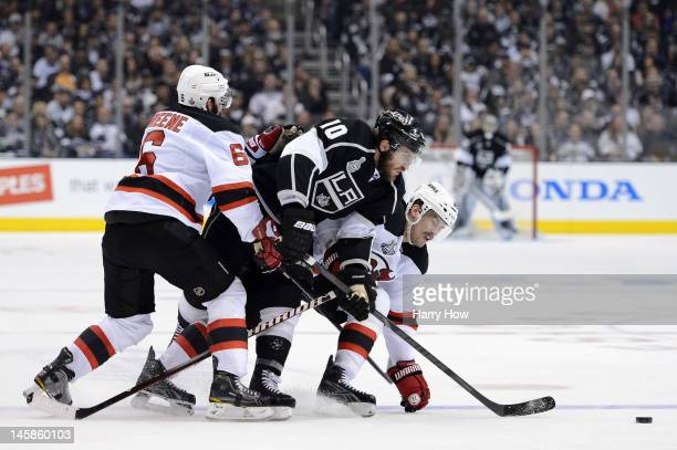 Mike Richards of the Los Angeles Kings skates for the puck over Adam Henrique and Andy Greene of the New Jersey Devils in Game Four of the 2012...