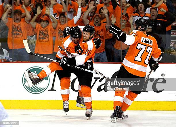 Mike Richards of the Philadelphia Flyers celebrates with teammates Ryan Parent and Claude Giroux after scoring a goal in the first period against...