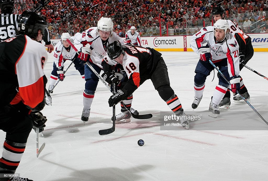 Mike Richards #18 of the Philadelphia Flyers faces off against Nicklas  Backstrom #19 and