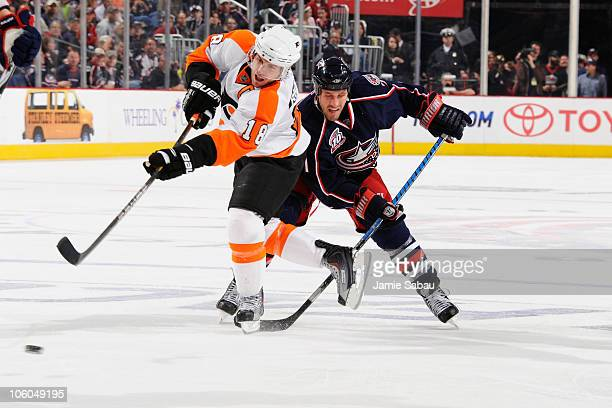 Mike Richards of the Philadelphia Flyers fires a shot before Chris Clark of the Columbus Blue Jackets is able to knock the puck away during the...