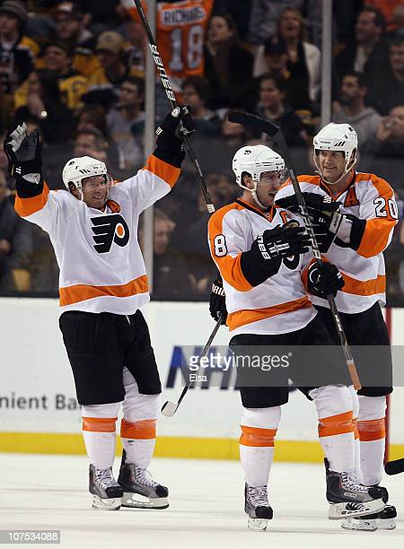 Mike Richards of the Philadelphia Flyers is congratulated by teammates Chris Pronger and Kimmo Timonen after Richards scored the game winning goal in...
