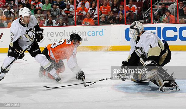 Mike Richards of the Philadelphia Flyers is interfered with by Andrew Hutchinson of the Pittsburgh Penguins while attempting a shot on goaltender...