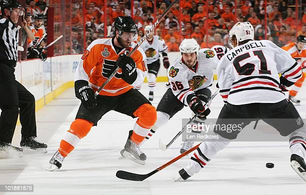 Mike Richards of the Philadelphia Flyers skates in on a loose puck against Dave Bolland and Brian Campbell of the Chicago Blackhawks in Game Four of...