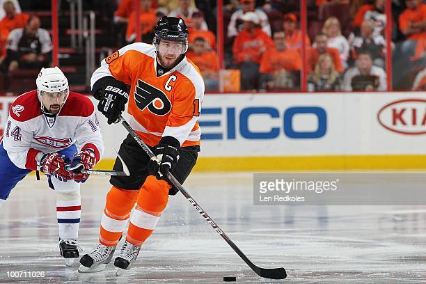 Mike Richards of the Philadelphia Flyers skates with the puck against Tomas Plekanec of the Montreal Canadiens in Game Five of the Eastern Conference...