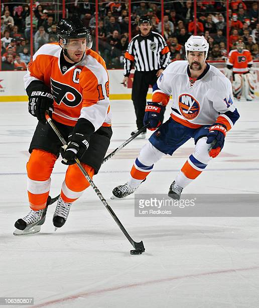 Mike Richards of the Philadelphia Flyers skates with the puck while pursued by Trevor Gillies of the New York Islanders on October 30 2010 at the...