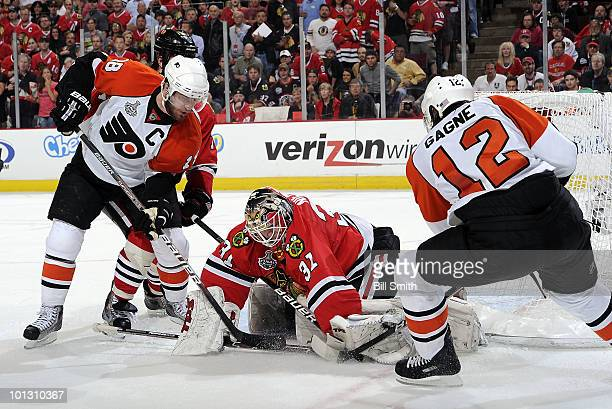 Mike Richards of the Philadelphia Flyers works to get the puck away from goalie Antti Niemi of the Chicago Blackhawks in Game Two of the 2010 Stanley...