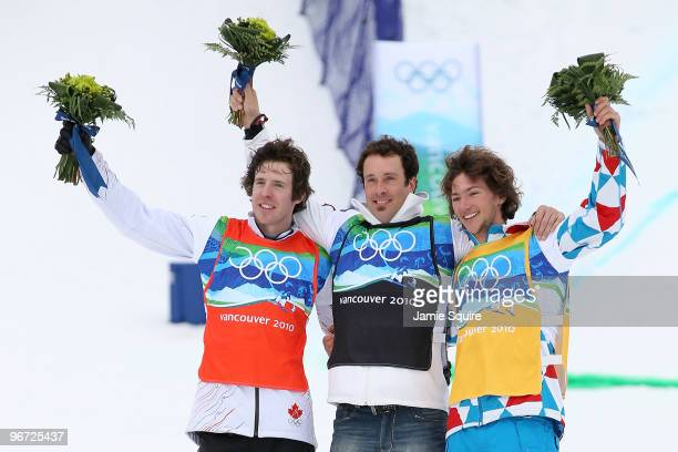 Mike Robertson of Canada celebrates winning silver, Seth Wescott of the United States gold and Tony Ramoin of France bronze during the flower...