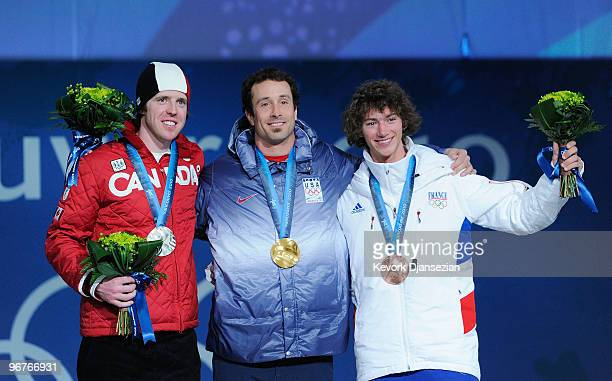 Mike Robertson of Canada celebrates winning the silver medal, Seth Wescott of the United States gold and Tony Ramoin of France bronze during the...