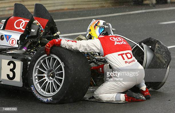 Mike Rockenfeller of Germany and Audi Sport Joest tries to fix his car after crashing during the Le Mans 24 Hour race at the Circuit des 24 Heures du...