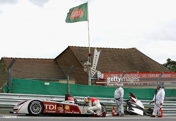 Mike Rockenfeller of Germany and Audi Sport Joest trys to fix his car after crashing during the Le Mans 24 Hour race at the Circuit des 24 Heures du...
