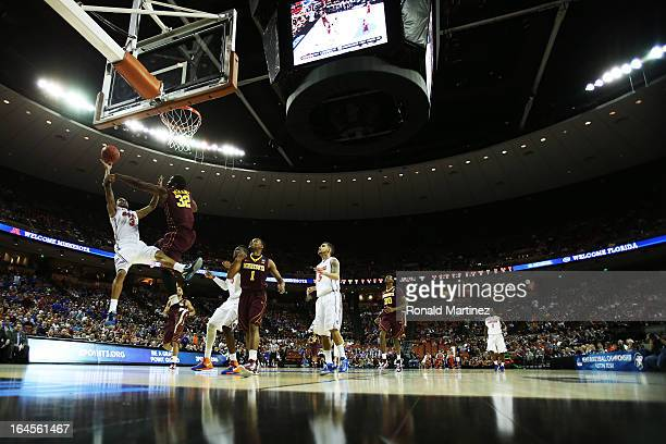 Mike Rosario of the Florida Gators goes up against Trevor Mbakwe of the Minnesota Golden Gophers in the first half during the third round of the 2013...