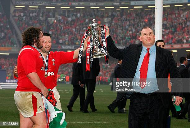 Mike Ruddock the Wales coach together with players Adam Jones and Mefin Davies raise the trophy as Wales' win the Grand Slam after defeating Ireland...