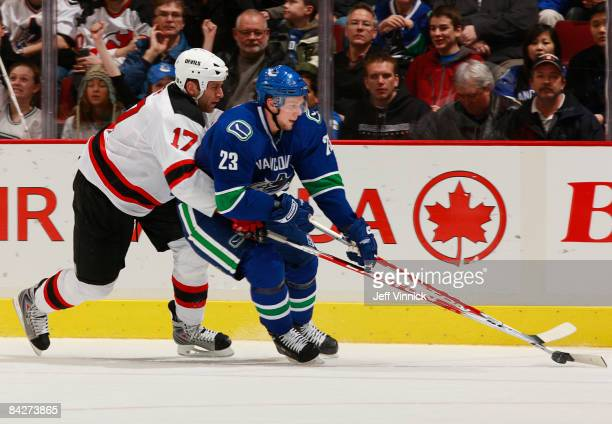 Mike Rupp of the New Jersey Devils reaches around Alexander Edler of the Vancouver Canucks during their game at General Motors Place on January 13...