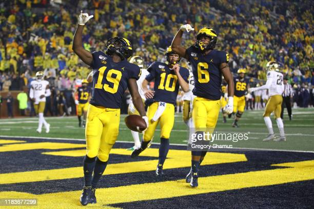 Mike Sainristil of the Michigan Wolverines celebrates his second half touchdown with teammates while playing the Notre Dame Fighting Irish at...