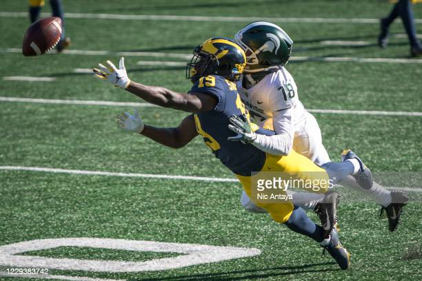 Mike Sainristil of the Michigan Wolverines fails to receive a pass while being covered by Kalon Gervin of the Michigan State Spartans during the...