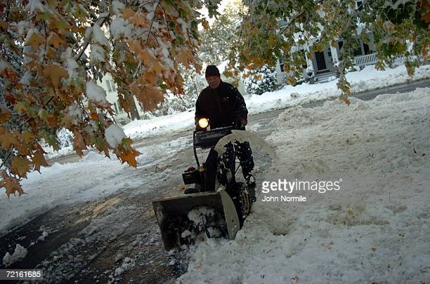 Mike Santaro clears snow October 13, 2006 outside of Buffalo in Orchard Park, New York. A rare and record breaking early season snowfall closed a 105...