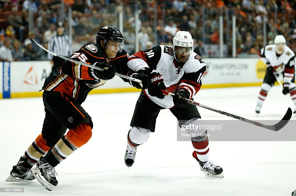 Mike Santorelli #25 of the Anaheim Ducks and Anthony Duclair #10 of the Arizona Coyotes skate to the puck during the second period of a game at Honda Center on October 14, 2015 in Anaheim, California.