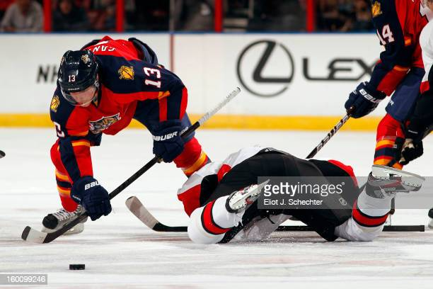 Mike Santorelli of the Florida Panthers tangles with Peter Regin of the Ottawa Senators at the BB&T Center on January 24, 2013 in Sunrise, Florida.