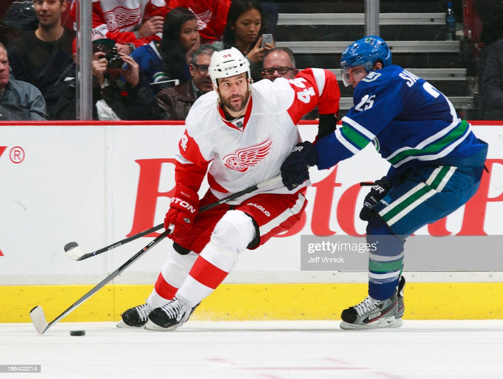 Mike Santorelli #25 of the Vancouver Canucks checks Todd Bertuzzi #44 of the Detroit Red Wings as he skates up ice with the puck during their NHL game at Rogers Arena on October 30, 2013 in Vancouver, British Columbia, Canada. Detroit won 2-1.